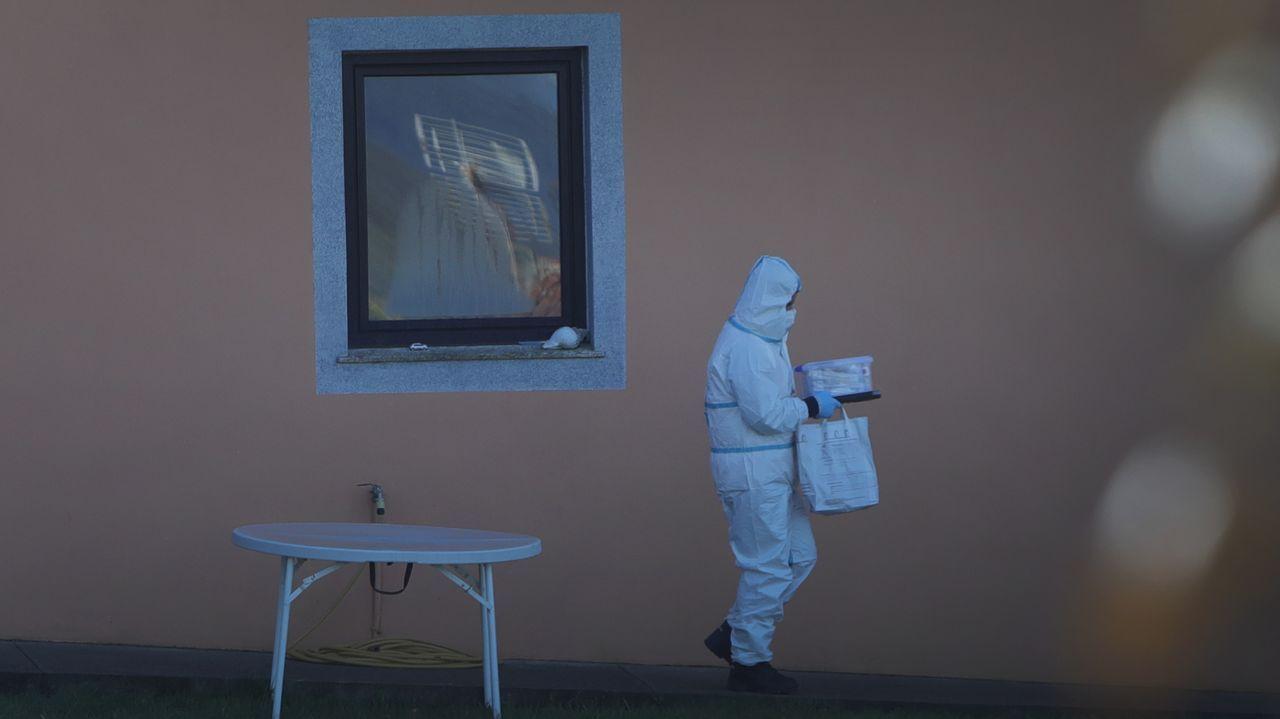 Un investigador de la policía buscando pruebas en la vivienda de la víctima, en Porzomillos