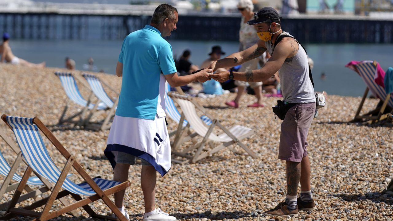 Arte, oración y colas para ir a la playa.Un hombre cobra el servicio de una tumbona a un bañista en la playa de Brighton