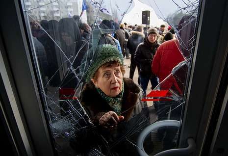 Una mujer se asoma a un edificio gubernativo de Donetsk, este de Ucrania, destrozado por prorrusos.