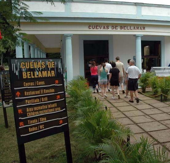 Edificio de acceso a las cuevas y viñetas de J. Riobó con Santos descubriendo las cuevas para el turismo