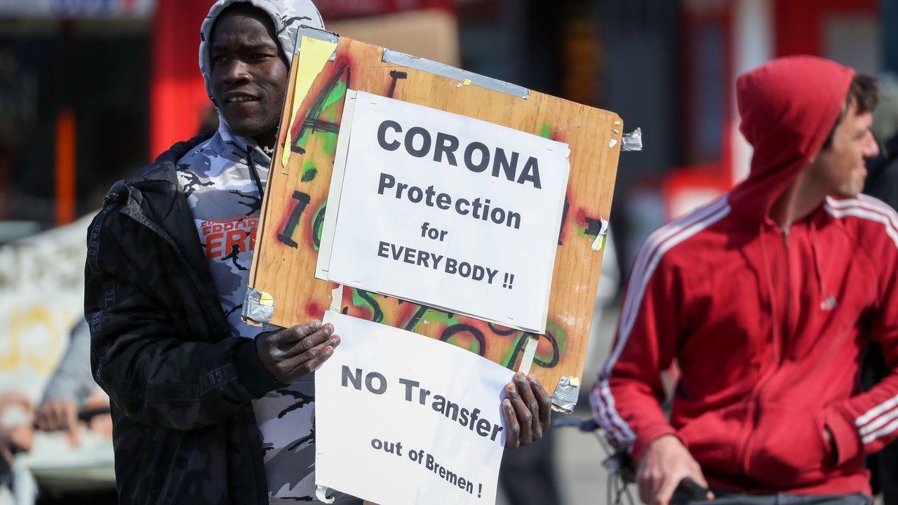 Un manifestante protesta contra el traslado de migrantes de un centro de Bremen, en Alemania, en plena crisis del coronavirus