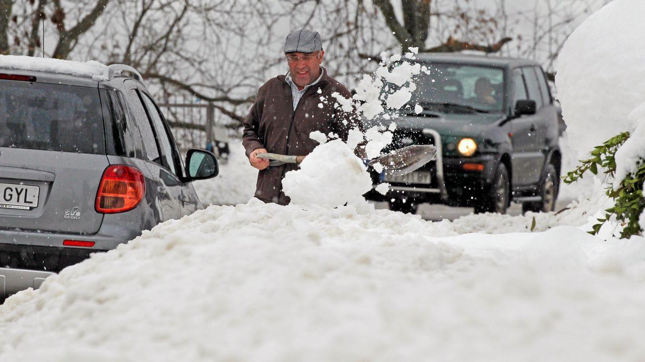 Jornada de alertas en Galicia.Un vecino del pueblo de Pajares trata de sacar su coche de la nieve