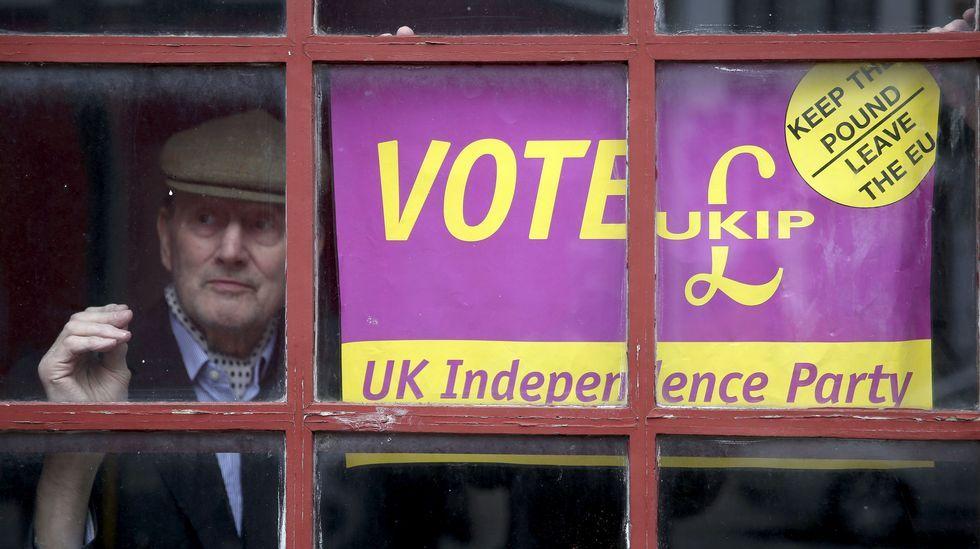 | EFE.Un hombre mira por la ventana junto a un cartel con dos propuestas del UKIP: mantenimiento de la libra y salida de la UE.