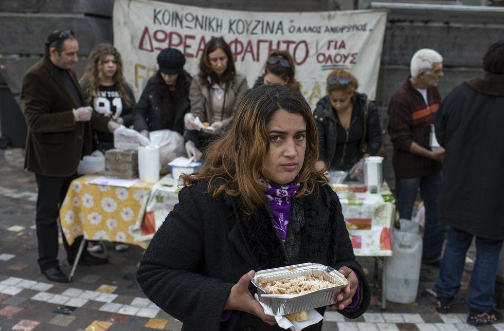 Pablo Iglesias se atreve con el griego.Una mujer en un puesto de reparto de comida, a cargo de una oenegé, en Atenas.