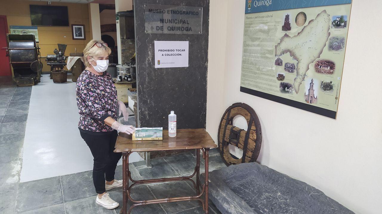 Mari Carmen Armesto, la trabajadora que está al cargo de los museos municipales de Quiroga, juno a una mesa con guantes de protección y gel hidroalcohólico que se ofrecen a los visitantes