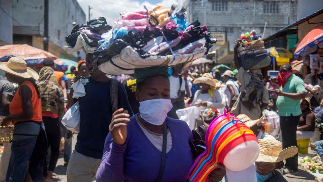 Una mujer camina portando mascarilla en una abarrotada calle comercial de Puerto Príncipe, a pesar de las restricciones impuestas para frenar el covid-19