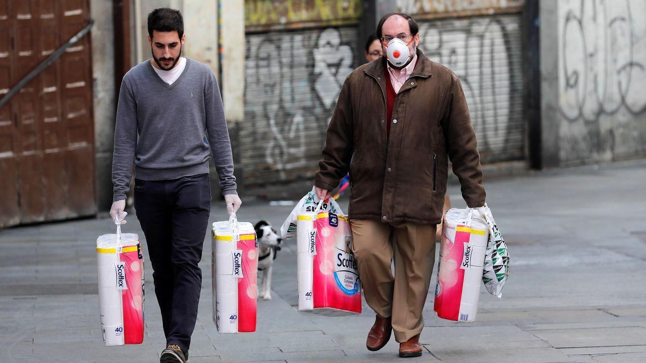 Dos compradores se aprovisionan de papel higiénico en el centro de Madrid