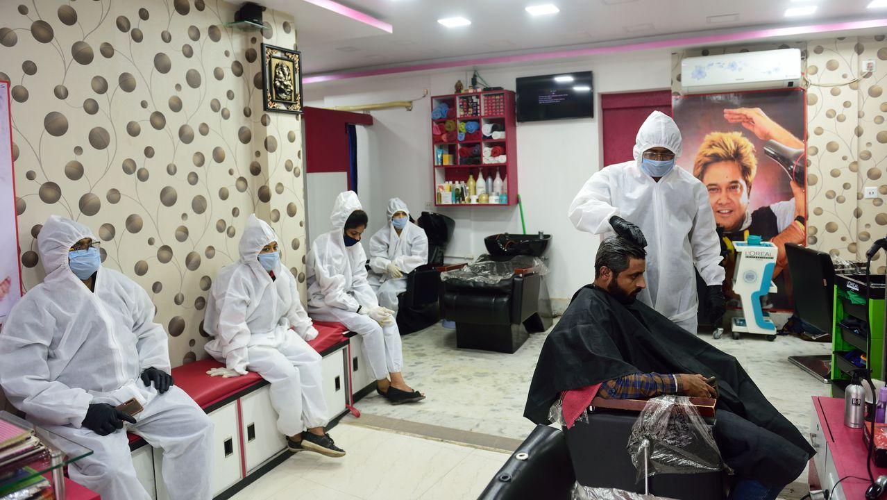En Calcuta, un peluquero corta el pelo a un cliente mientras otros aguardan vestidos con trajes de protección