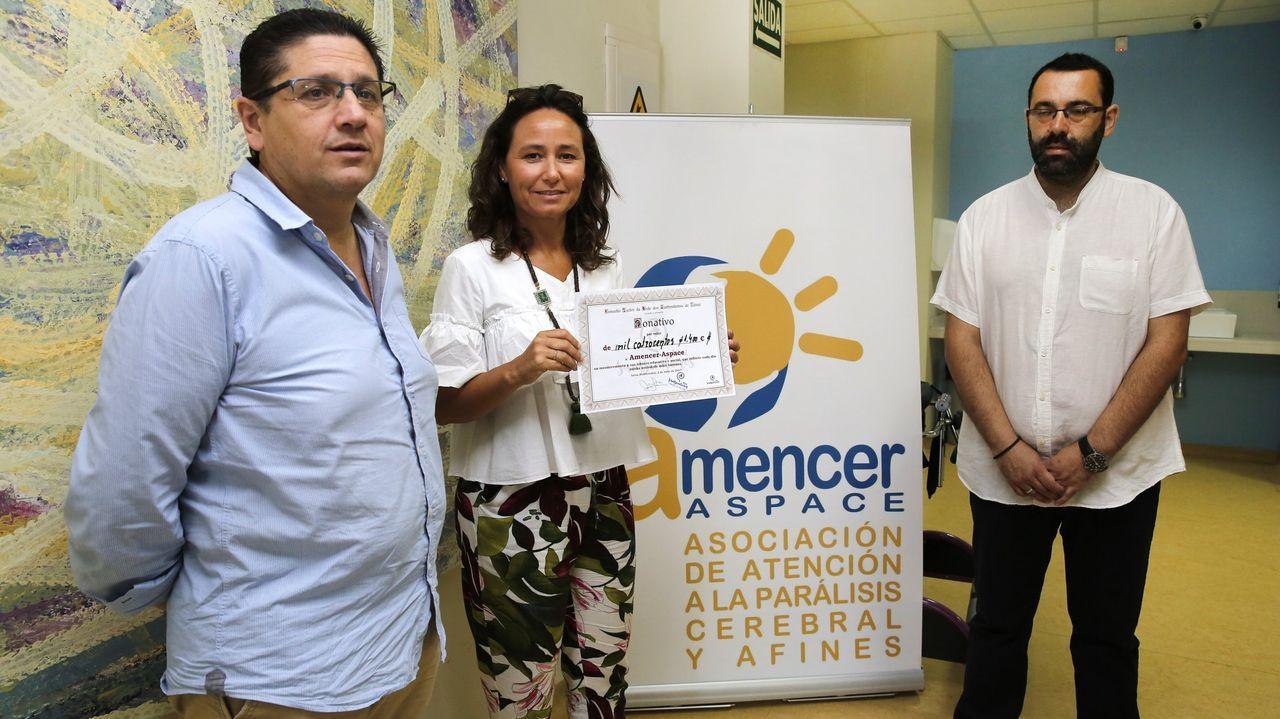 Mónica Touriño, en el centro, gerente de la asociación Amencer-Aspace, en una imagen de archivo recibiendo una donación de Lérez