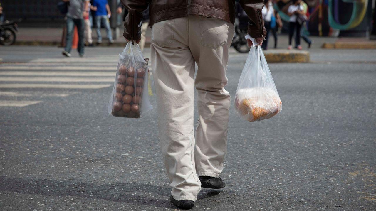 Un hombre camina con bolsas de alimentos por una calle de Caracas