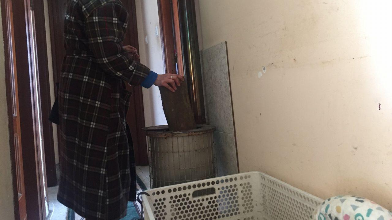 Una mujer echa leña a la estufa con la que se calienta