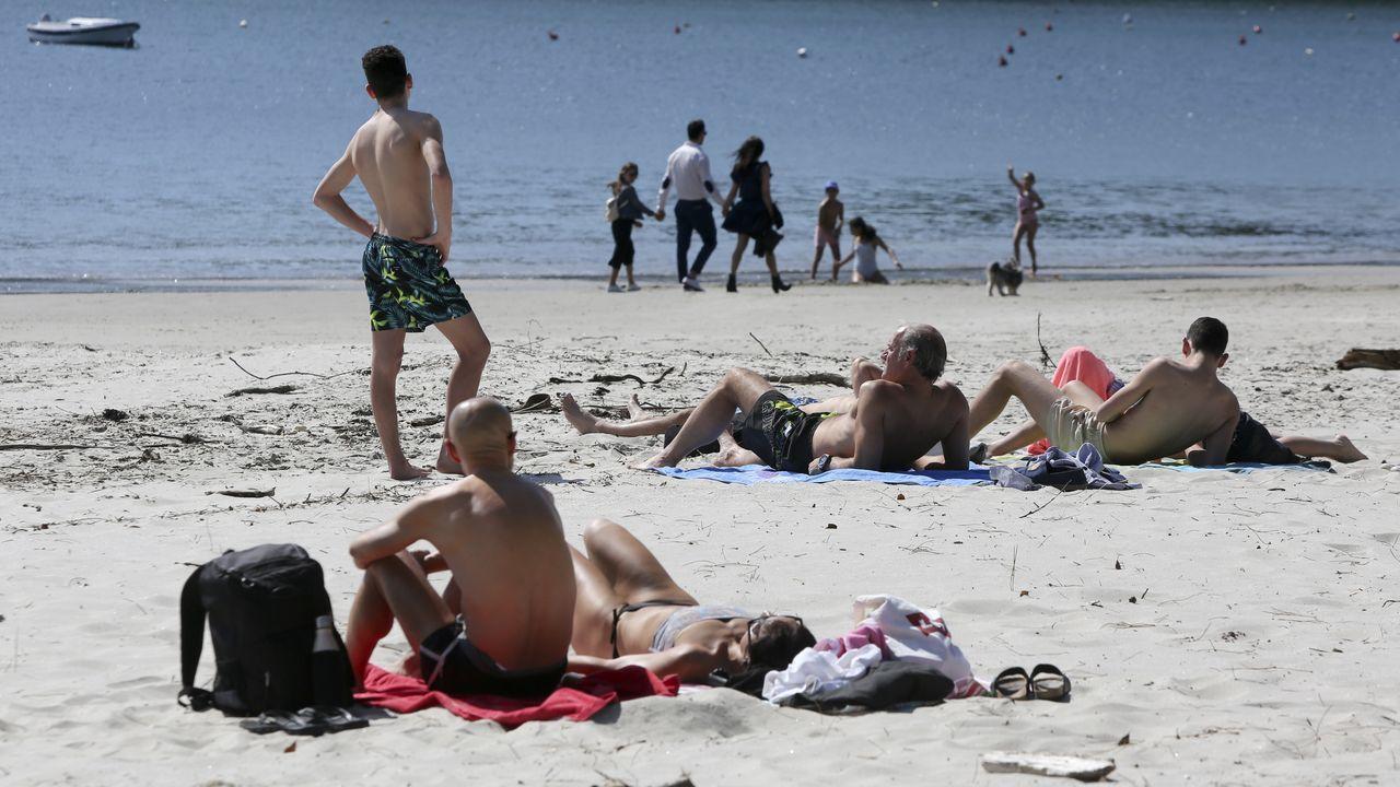 Gente tomando el sol, pese a que no está permitido, en la playa de Doniños