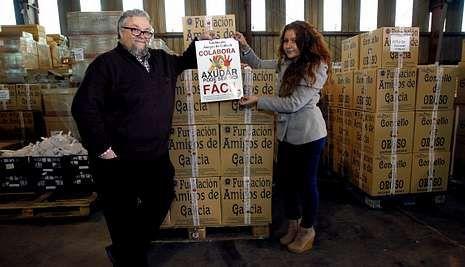 El actor, con Noelia Romero y con los paquetes de alimentos en la nave de la fundación.