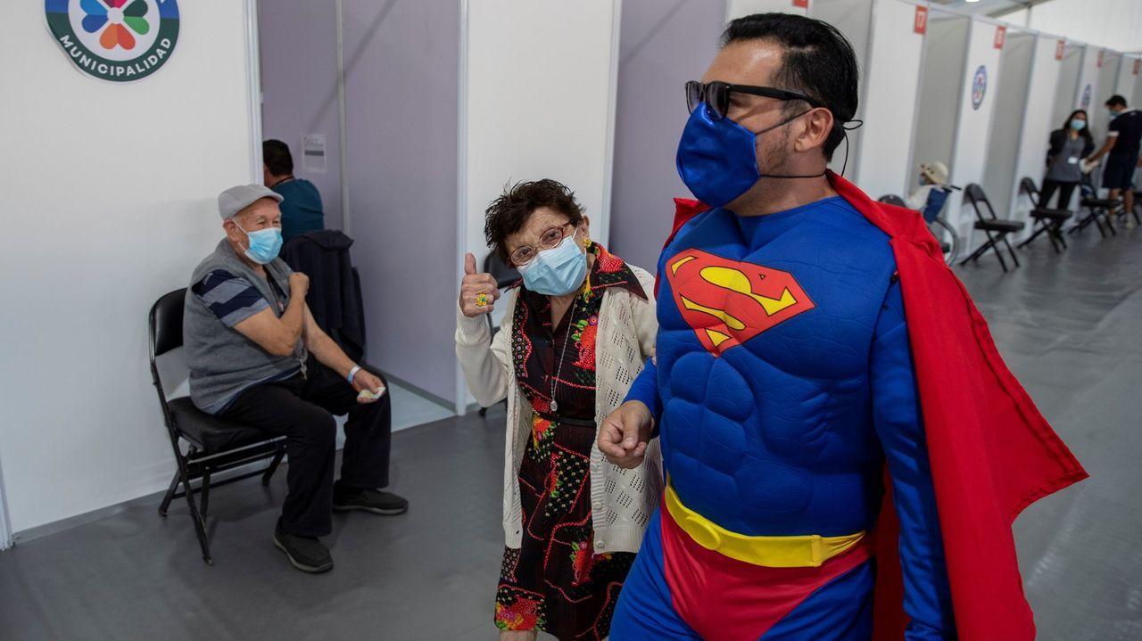 Un hombre vestido de Superman acompaña a su madre a vacunarse en un centro de salud de Santiago de Chile