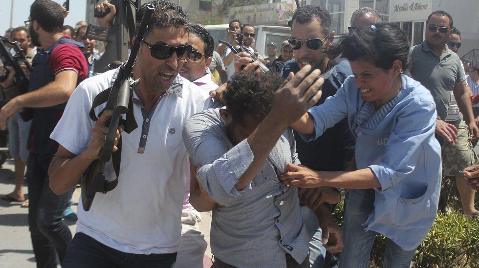 Gran ceremonia para inaugurar el nuevo canal de Suez.Un policía controla la multitud que intenta agredir a un sospechoso de estar involucrado en el ataque al hotel Riu en Port el Kantaui en la costa tunecina.