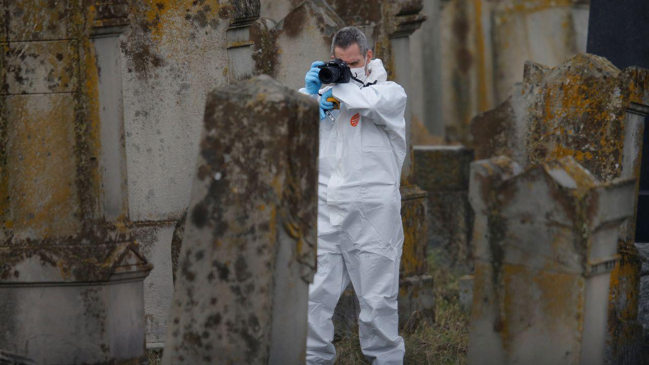 Un investigador toma foto de una de las tumbas que objeto de las pintadas