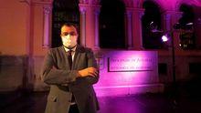 El presidente del Principado, Adrián Barbón, ante el edificio de Presidencia iluminado en morado