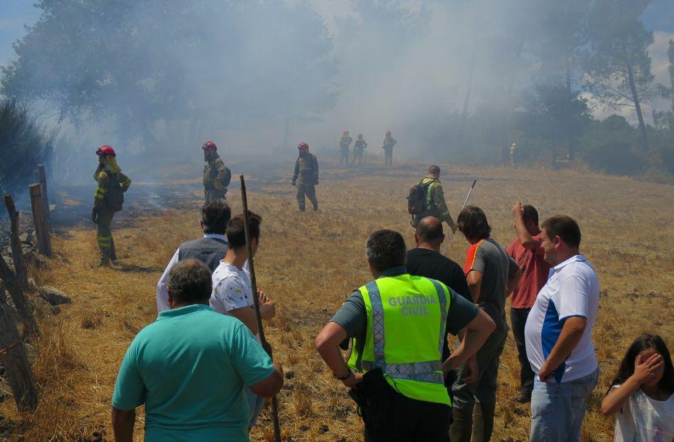 Comienza el certamen celtibérico infantil de bandas de gaitas.Un guardia Civil y varios vecinos, en un prado junto al incendio en el que trabajan los brigadistas.