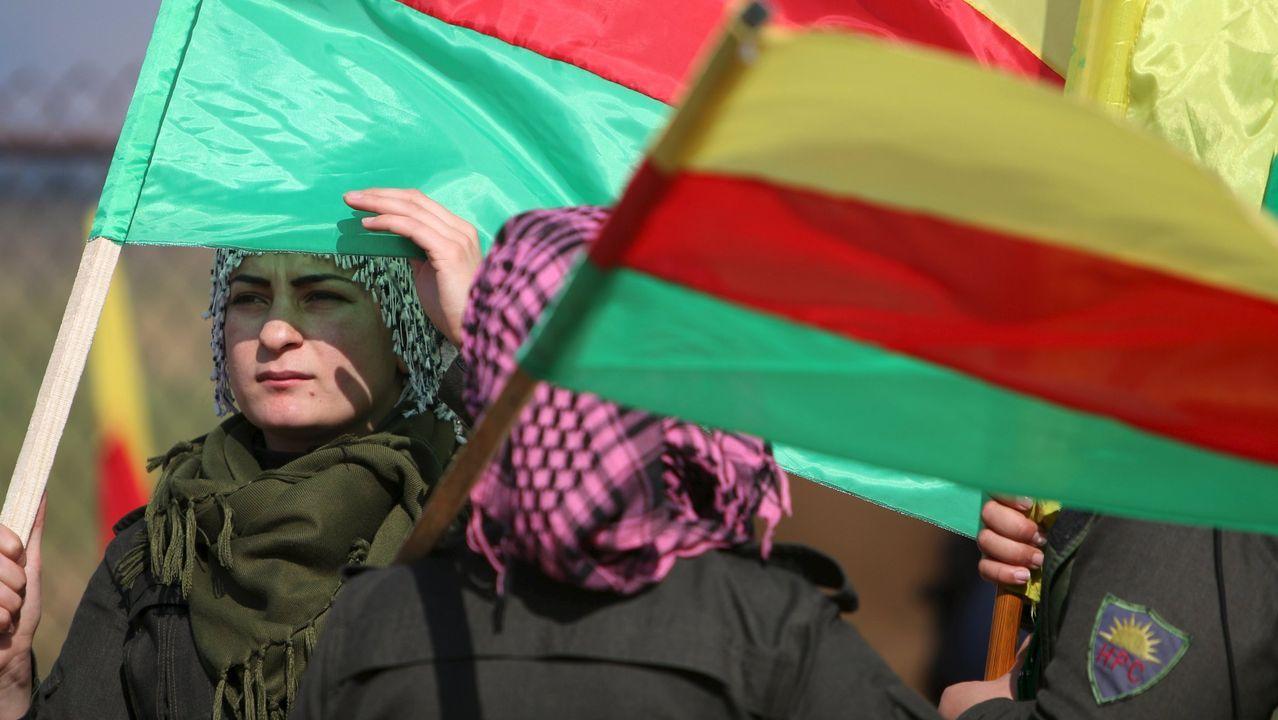 Milicianas de las fuerzas kurdas portan banderas del Kurdistan sirio o  Rojava