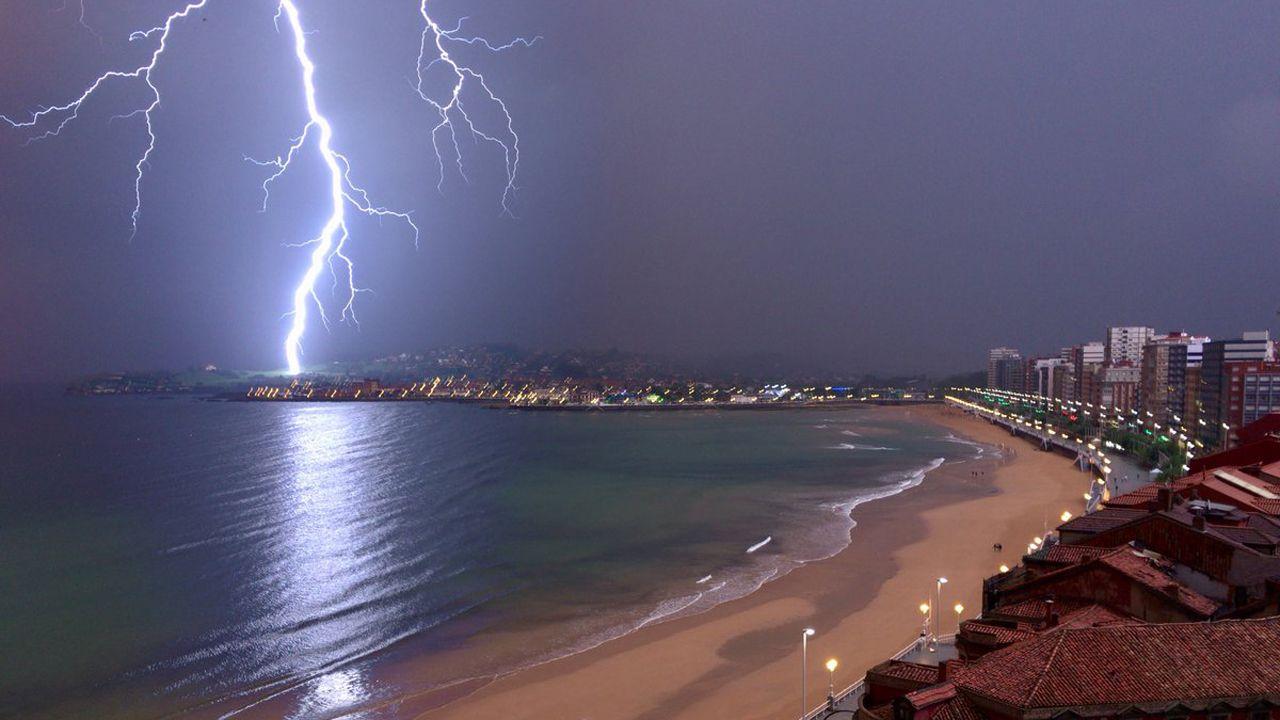 «Brigadas de limpieza» retiran lazos amarillos en varias localidades catalanas.Un rayo ilumina la playa de San Lorenzo, en Gijón