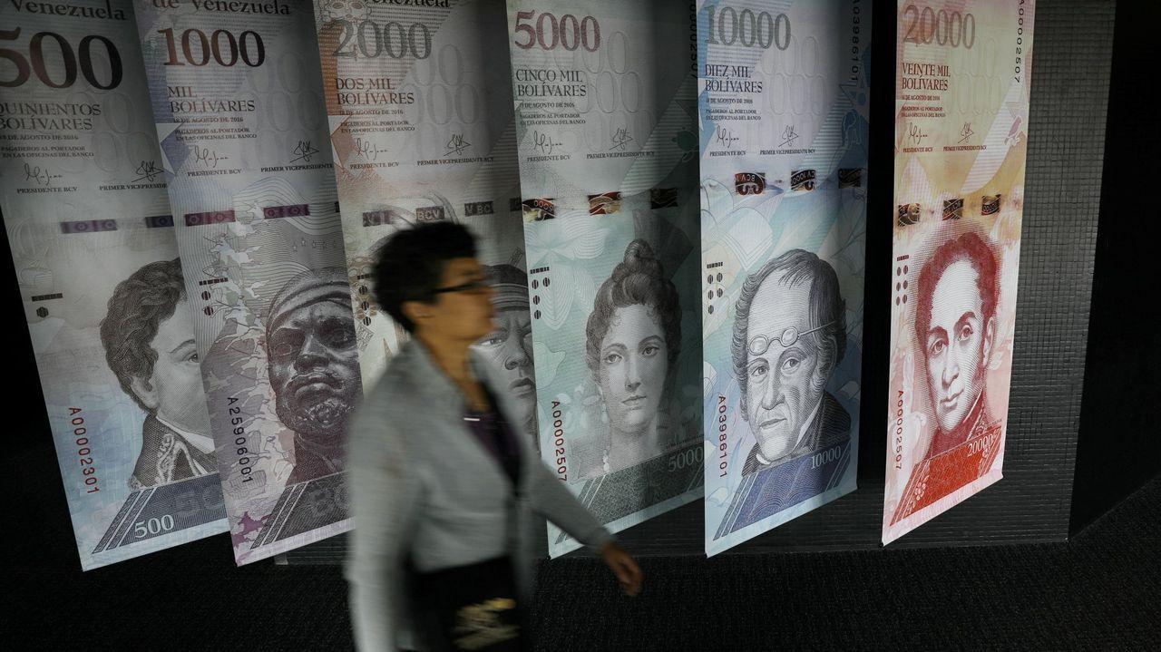 Una mujer pasa por un muestrario de los nuevos billetes de bolívares que se exhibe en la sede del Banco Central de Venezuela