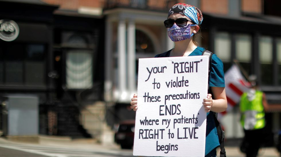 Una sanitaria de Boston responde a una manifestación contra el confinamiento con una pancarta que dice: «Tu  derecho  a violar estas precauciones termina donde empieza el derecho de mis pacientes a vivir»