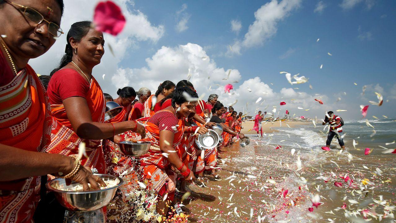 Lunes de escuela, parque de atracciones ycoronavirus.Un grupo de mujeres esparcen pétalos de flores en Bengala en homenaje a las víctimas