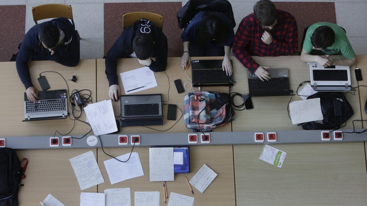 Alumnos con ordenadores y apuntes a mano en la facultad de Informática de Elviña