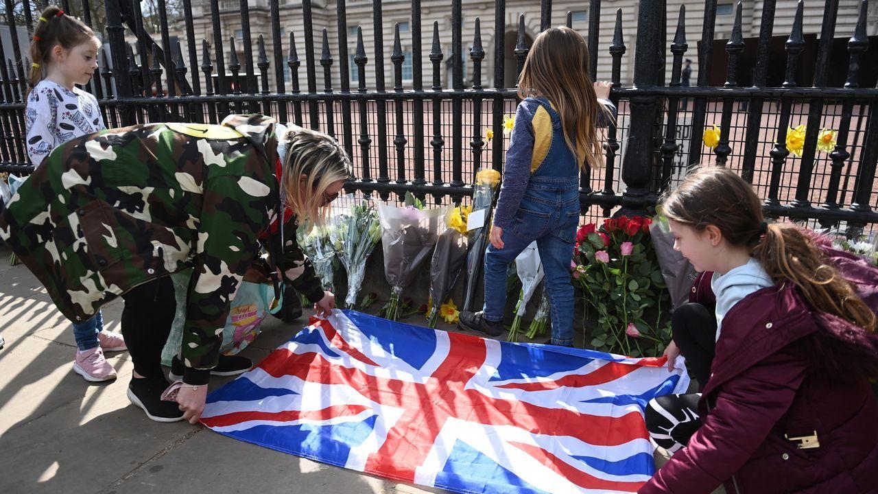 Gente colocando la bandera británica junto a flores y mensajes de condolencia en el exterior del Palacio de Buckingham, tras el fallecimiento del príncipe Felipe