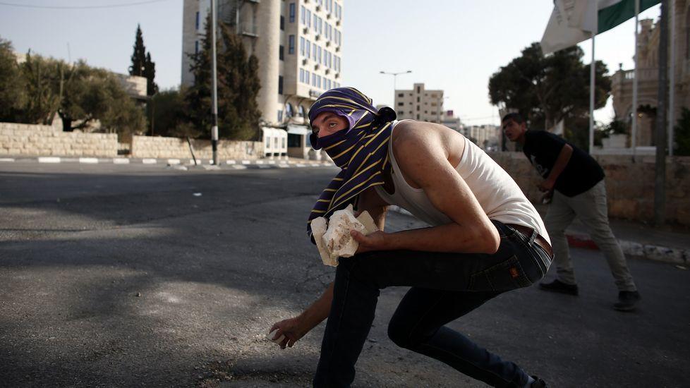 Dos palestinos enmascarados se cubren tras lanzar piedras contra los soldados israelíes.