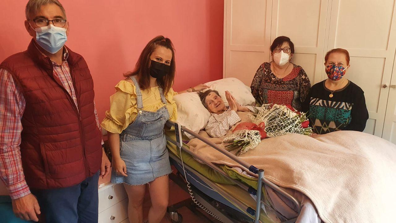 De izquierda a derecha, José Manuel, amigo y enfermero de la centenaria; Noelia, la nieta de Ramona (en cama); Fina, una vecina; e Isabel, la hija de la homenajeada