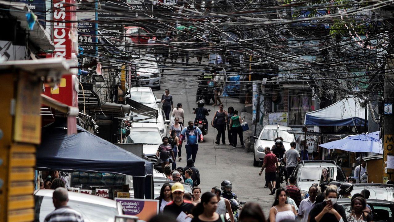 Grupos de personas caminan por la favela de Rocinha, en Río, donde las personas mayores se resisten a aceptar la invitación del alcalde a confinarse en hoteles con gastos pagados