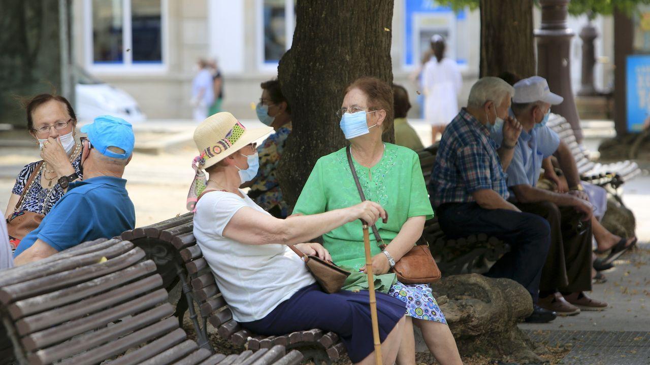 Gente mayor resguardada del sol en los bancos de la Praza Maior