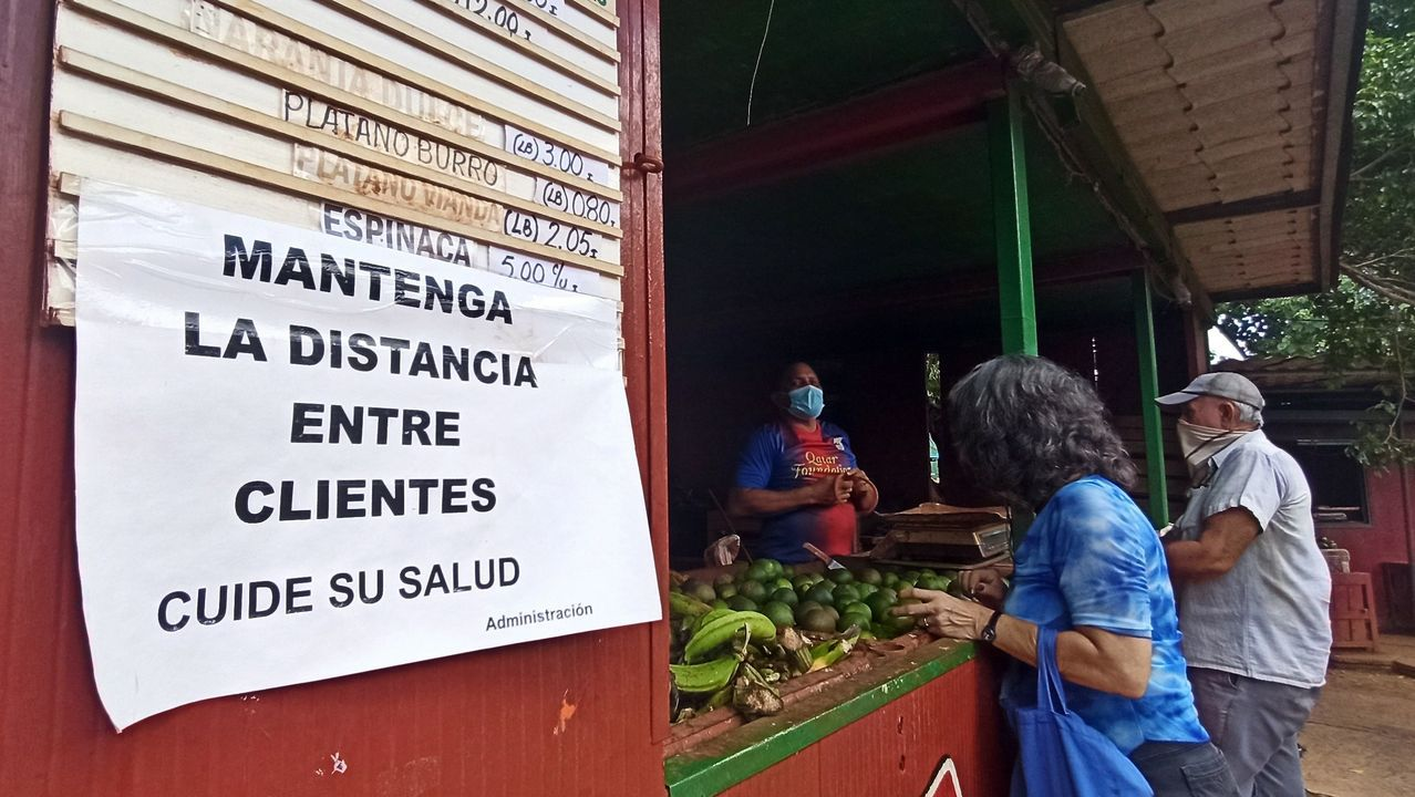 Dos personas con tapabocas hacen compras en un mercado donde se lee un cartel del cuidado de la distancia social este, en La Habana, Cuba