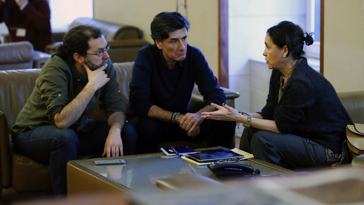 La consejera de Hacienda del Principado, Dolores Carcedo (d), el portavoz de Podemos, Emilio León (i) y el diputado de este partido, Enrique López (c), conversan durante el pleno de la Junta General