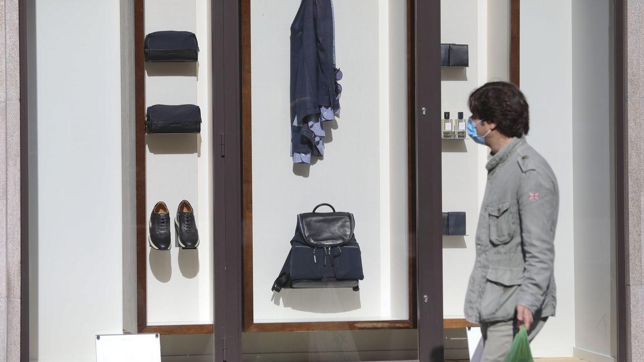Un compostelano observa el escaparate de una tienda que reabrirá la semana que viene