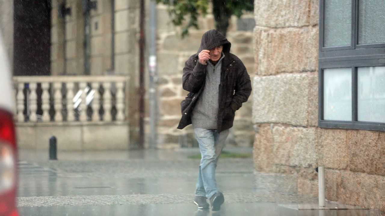 Un hombre se protege del mal tiempo en Arousa