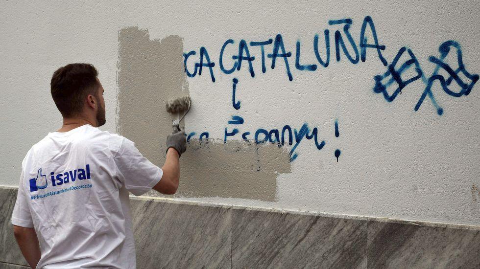Un operario de la brigada de limpieza borra una pintada en el colegio electoral situado en el Centro Cultural Mira-sol de San Cugat, donde ha votado el cabeza de lista de Junts pel Sí, Raül Romeva