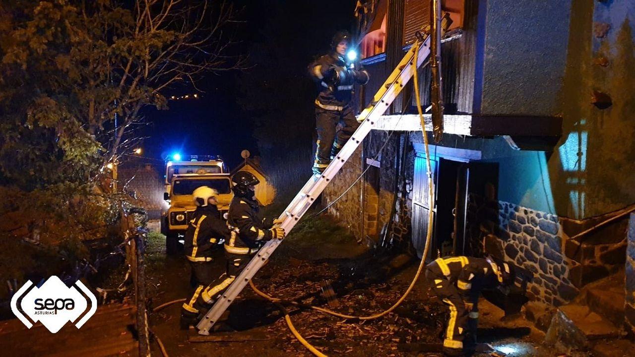 Los bomberos tratan de apagar el fuego en una vivienda unifamiliar de Piloña