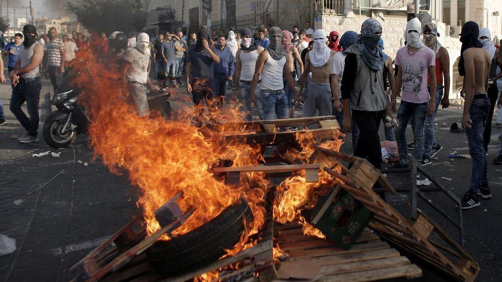 Palestinos agrupados tras una barrera de madera ardiendo.