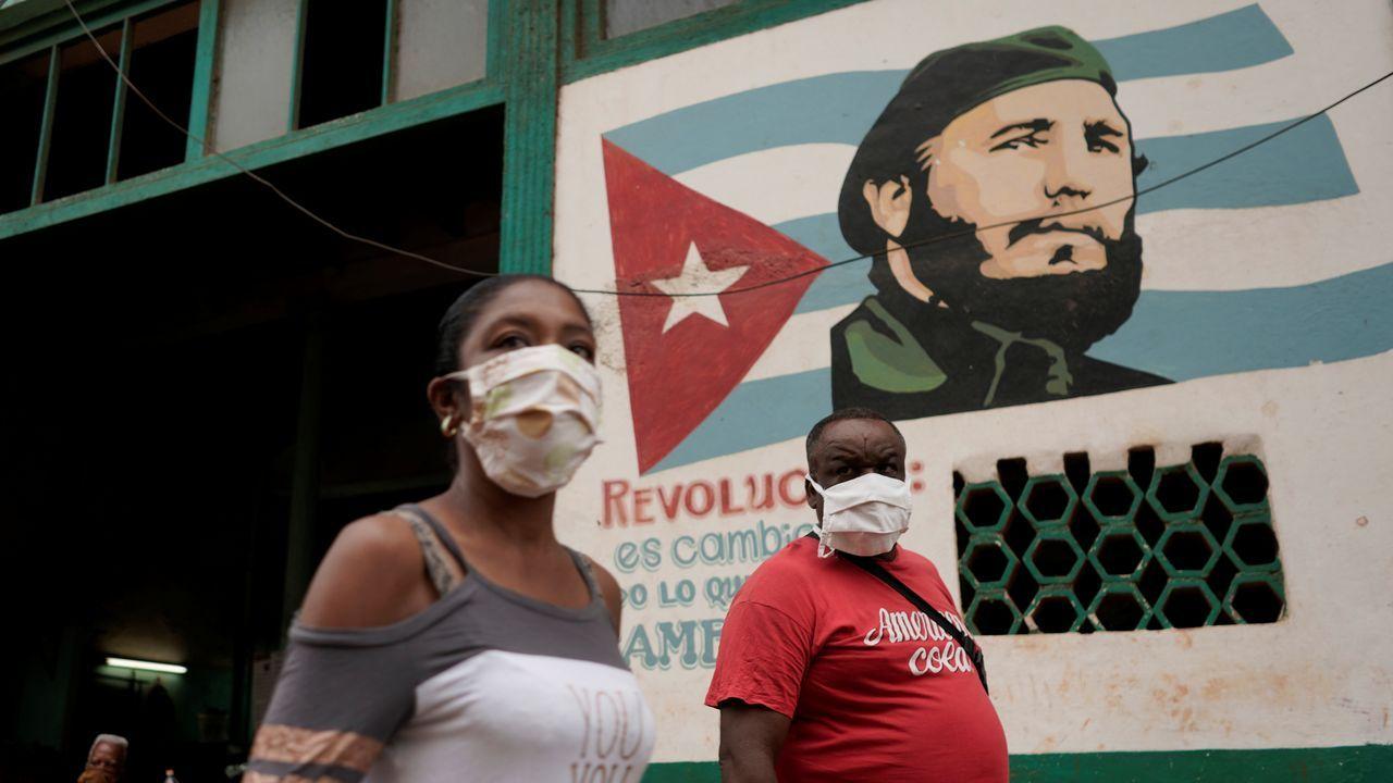 Meat Butik.Gente pasa junto a una imagen del fallecido presidente cubano Fidel Castro, en La Habana, Cuba