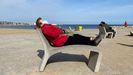 Una mujer descansa en un banco de la Barceloneta