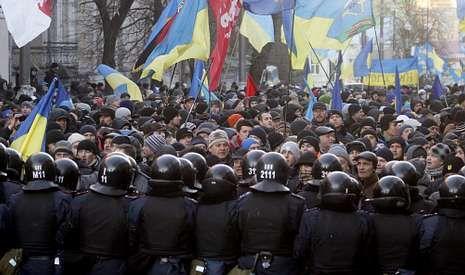 Una barrera de policías contiene a los ucranianos que se congregaron frente al Parlamento durante la moción de censura.