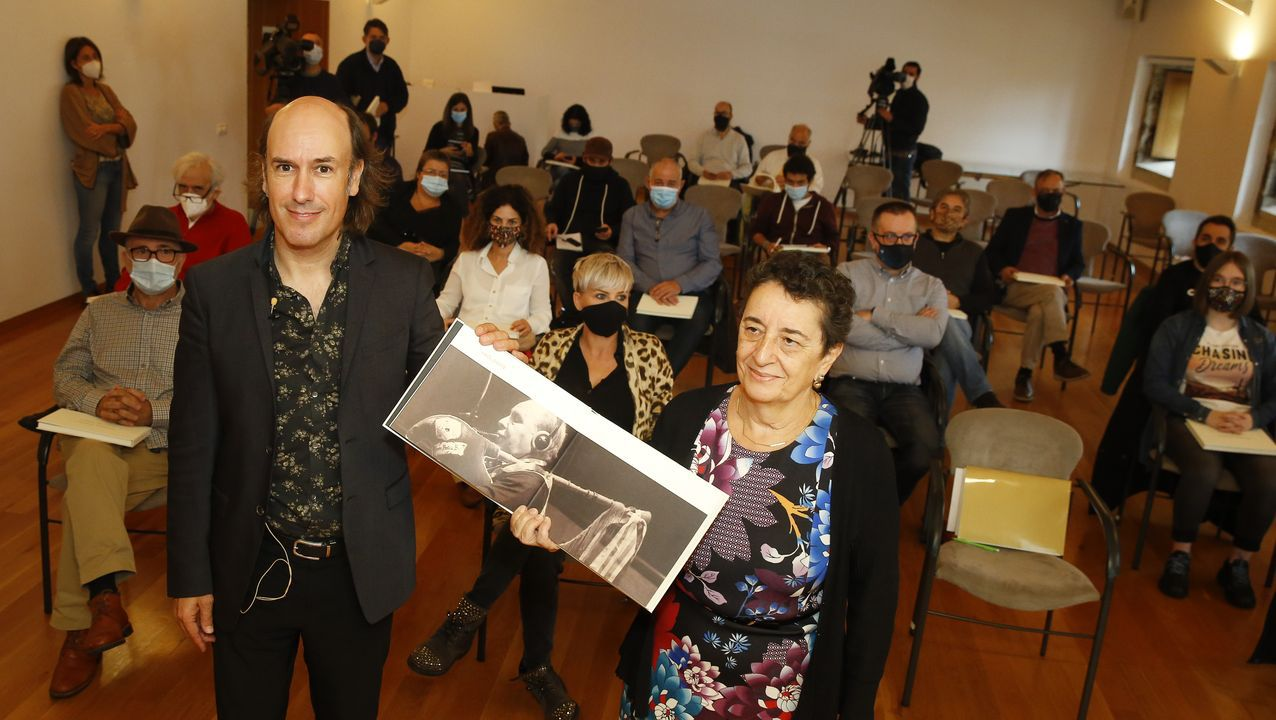 A presidenta do CCG, Rosario Álvarez, e o músico Carlos Núñez, mostran o libro sobre Portela