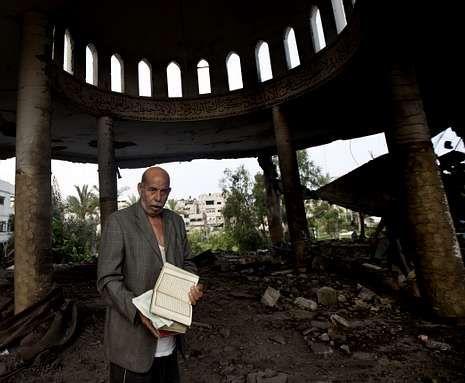 Un palestino recupera la copia de un Corán en la mezquita bombardeada ayer en Gaza.