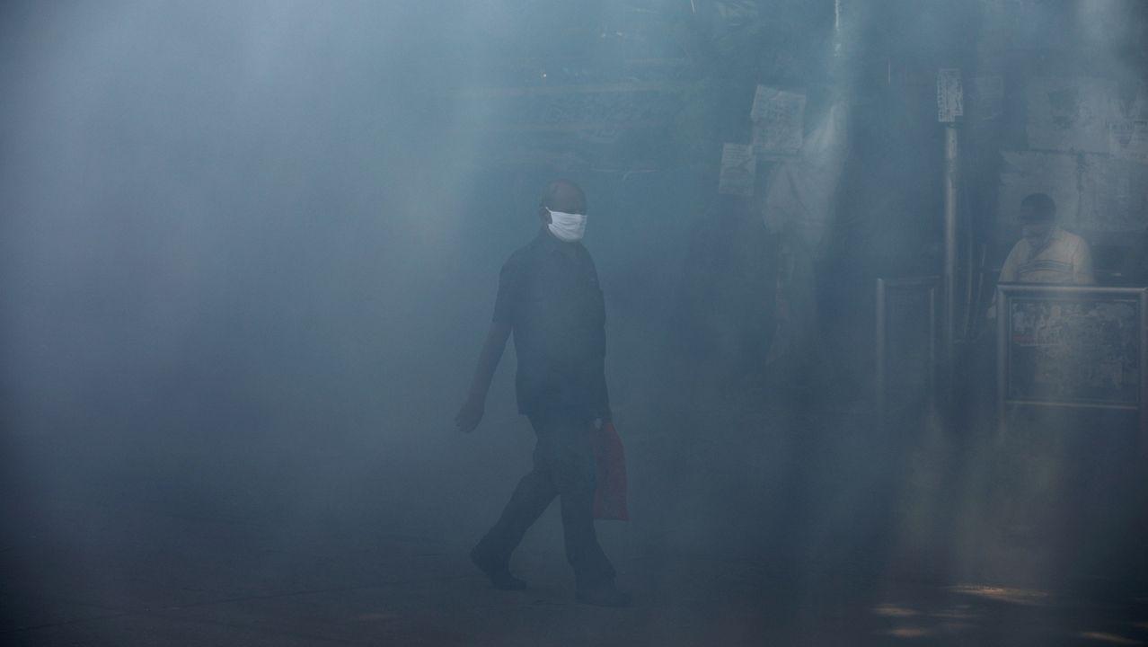 Un hombre camina por una calle fumigada en Bombai
