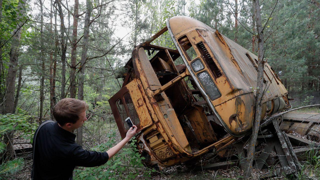 Un visitante toma una foto a un autobús abandonado en la zona de exclusión de Chernóbil