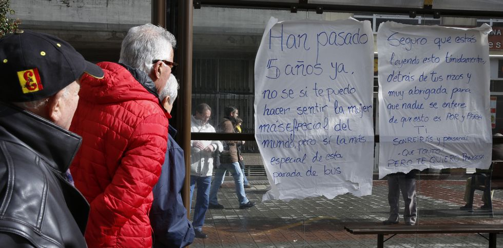 Vecinos de los Castros leen el mensaje que apareció ayer pegado en la parada del bus.