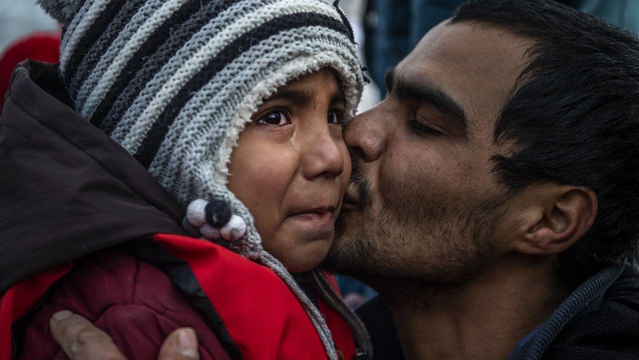 Un hombre besa a una niña que llora en la isla griega de Lesbos