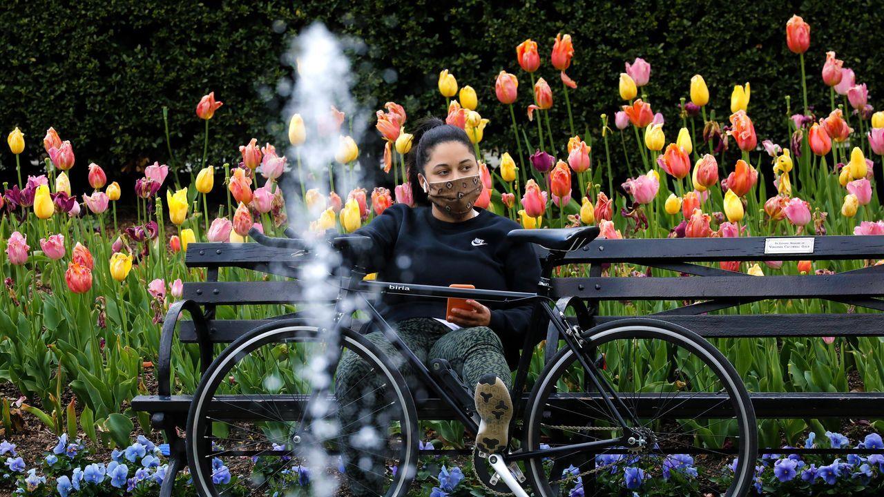 Una mujer descansa en Central Park vestida con mascarilla, como ordenan las leyes locales